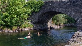 Father and teen children swimming in the River Duddon by old sto. Ne bridge in Ulpha in the Lake District National Park, UK. Scenic view of English countryside Stock Photo