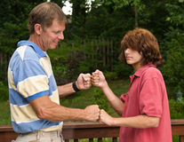 Father and teen son fist-bumping Stock Photography