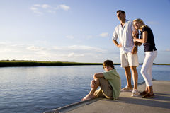 Father and teenage children on dock by water Stock Image