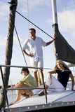 Father and teenage children on sailboat at dock Stock Images
