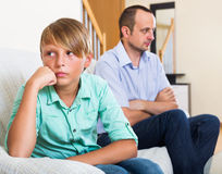 Father and teenage son argue. Ordinary father and teenage son in the middle of argue in home Stock Image