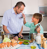 Father and teenage son cooking together Stock Images