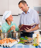 Father and teenage son cooking together Stock Photo