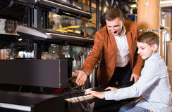 Father and teenage son examining keyboards in guitar shop. Happy english father and teenage son examining keyboards in guitar shop Royalty Free Stock Image