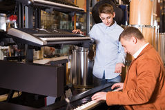Father and teenage son examining keyboards in guitar shop. Happy european father and teenage son examining keyboards in guitar shop Stock Photos