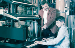 Father and teenage son examining keyboards in guitar shop. Happy germany father and teenage son examining keyboards in guitar shop Royalty Free Stock Image
