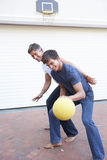 Father And Teenage Son Family Playing Basketball Outside Garage Royalty Free Stock Images