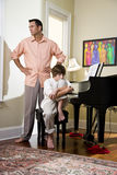 Father and teenage son at home upset. Upset father standing beside teenage son at home Stock Images