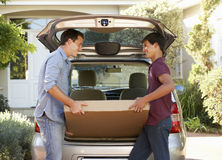 Father And Teenage Son Loading Large Package Into Back Of Car Royalty Free Stock Image