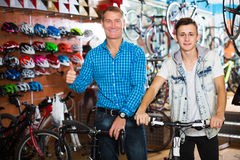 Father with teenager trying new bicycle Stock Photos