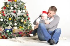Father and their small child sits near Christmas tree Royalty Free Stock Image