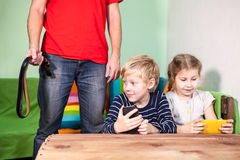 Father threatens with strap into kids. Punishment a child for spending amount of time in game with cellphones Royalty Free Stock Image
