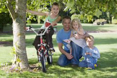 Father with three children (3-9) kneeling on grass beside tree in garden, girl sitting on bike, smiling, front view, portrait Stock Image