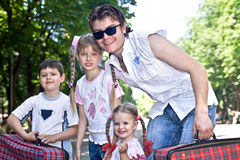 Father and three children in park with case. Father and group children in park with case.Outdoor Stock Photography