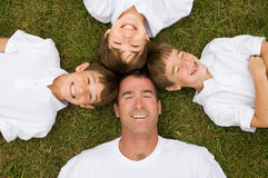 Father and Three Sons. Laying in Grass Laughing stock image