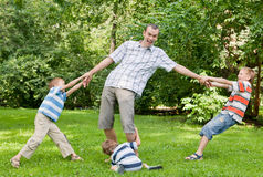 Father and three sons play in the park. Royalty Free Stock Image