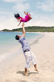 Father throw daughter in the air at beach Stock Images