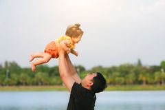 Father throw up daughter in the air on the park. Father throw up daughter in the air on the park royalty free stock images