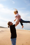 Father throwing daughter in the air at the beach Stock Photography