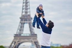 Father throwing his little son in the air near the Eiffel tower Royalty Free Stock Photos