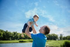 Father throwing his little son up in the air. Family time together. Happy little boy having fun with his dad. Outdoors stock images