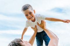 Father throwing his little son up in the air. Family time together. Happy little boy having fun with his dad outdoors. Father throwing his little son up in the Stock Photos