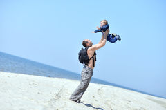 Father throwing his son up on the sea coast in summer Stock Images