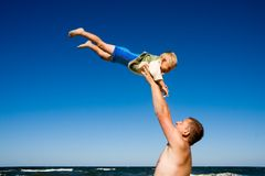 Father throwing son on beach Royalty Free Stock Photo
