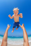 Father throwing up in the air a happy child. Family swimming fun on white sand sea beach and blue sky - father hands tossing up baby boy into mid air and Royalty Free Stock Images