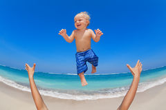 Father throwing up in the air a happy child Royalty Free Stock Photos
