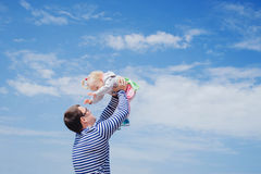 Father throwing up little daughter to the air stock image