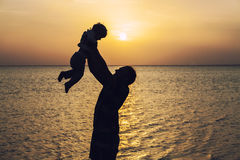 Father throwing young child silhouette on a background of dawn a Royalty Free Stock Image