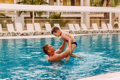 Father throws child in the pool royalty free stock images