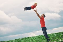 Father throws child into the sky, standing on a corn field. They dressed in the same clothes family look. Happy childhood concept royalty free stock images