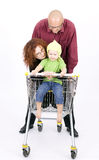 Father thrusting shop trolley, mother, daughter in Royalty Free Stock Image