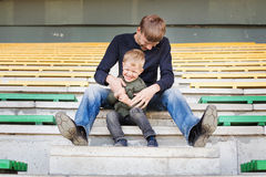 Father tickles his son. Father and son playing in empty stadium Royalty Free Stock Image