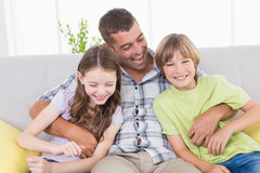 Father tickling children while sitting on sofa Royalty Free Stock Photos