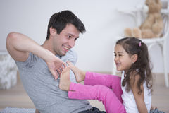 Father tickling daughter's foot at home Royalty Free Stock Photos