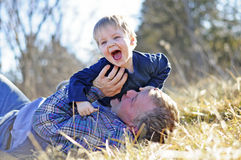 Father tickling son outdoors Royalty Free Stock Photo