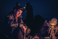 Father and son sitting by the campfire in outdoors camp in the night after long hunting day stock images