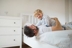 Father with a toddler boy having fun in bedroom at home at bedtime. Mature father with a toddler boy having fun in bedroom at home at bedtime. Paternity leave Royalty Free Stock Photos