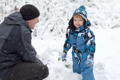 Father and toddler boy having fun with snow Stock Photos