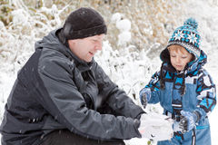 Father and toddler boy having fun with snow Royalty Free Stock Photography
