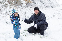Father and toddler boy having fun with snow on winter day Royalty Free Stock Photo