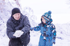 Father and toddler boy having fun with snow on winter day Stock Images