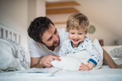 Father with toddler boy reading a book on bed at home at bedtime. Mature father with toddler boy in bedroom at home, reading stories at bedtime. Paternity leave Stock Photo