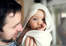 Father with a toddler child wrapped in towel in a bathroom at home. Father with an happy toddler child wrapped in a towel in a bathroom at home. Paternity leave stock photos