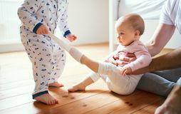 Father and toddler children sitting on the floor at home at bedtime. Royalty Free Stock Photo