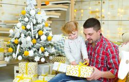 Father and toddler daughter opening gifts near Christmas tree stock photography