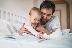 Father with toddler girl reading a book on bed at home at bedtime. Mature father with toddler girl in bedroom at home, reading stories at bedtime. Paternity Stock Images